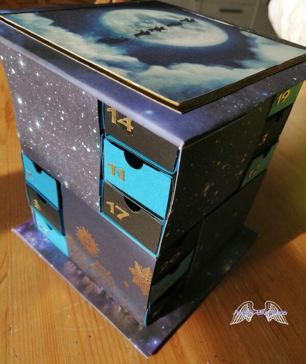Calendrier de l'avent en forme de tour avec des tiroirs en couleur bleu, noir, des étoiles et le père Noël dans le ciel 2